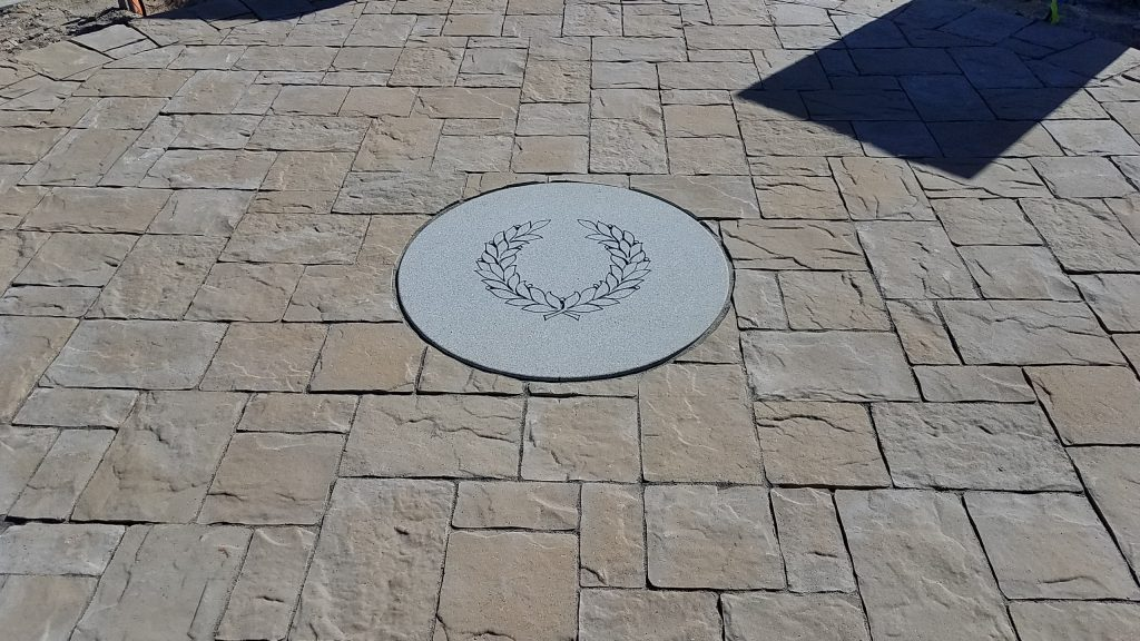 Douglasville's Military Honor Garden's victory wreath carved in a circular Georgia Granite medallion and place in the Belgard Mega-Lafitt paver walk.