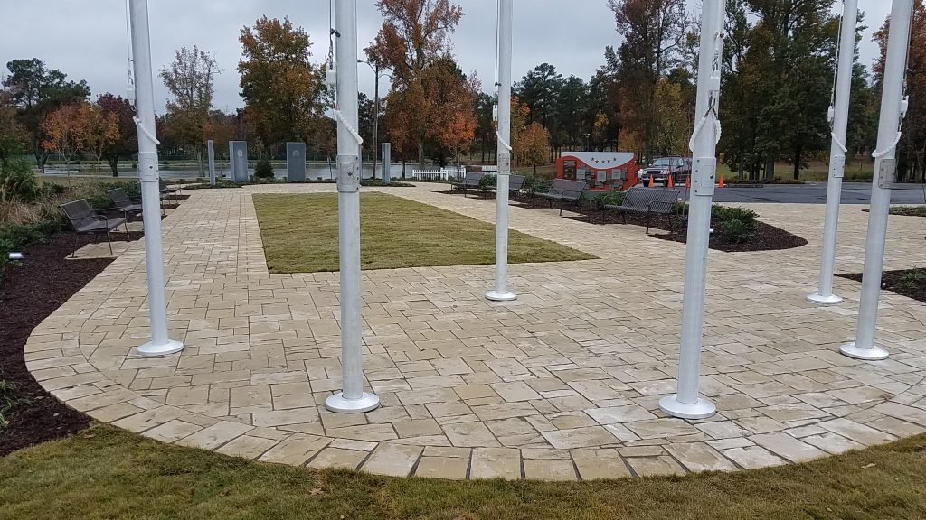 Belgard Mega Lafitt paver circular walk with flag poles in the Douglasville Military Honor Garden. Each representing a military branch surrounding the United States flag.