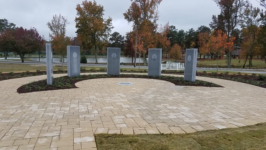 Southern ground level view of Douglasville Military Honor Garden. Georgia Granite monuments engraved with each military branch seal surrounding a victory wreath carved in a cicular Georgia Granite medallion.